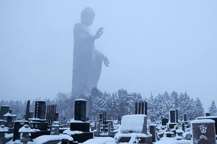 bouddha_géant_dominant_un_cimetière_enneigée.png