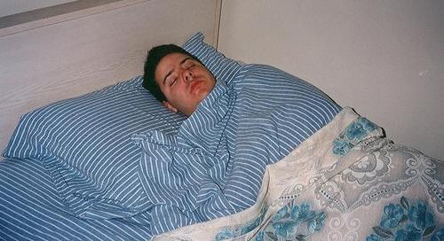 Man_sleeping_striped-sheets.jfif